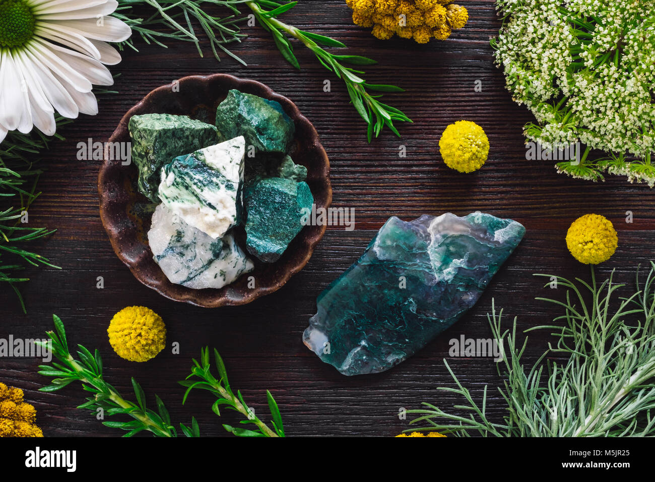 Tree Agate and Moss Agate with Mixed Botanicals on Dark Table - Stock Image