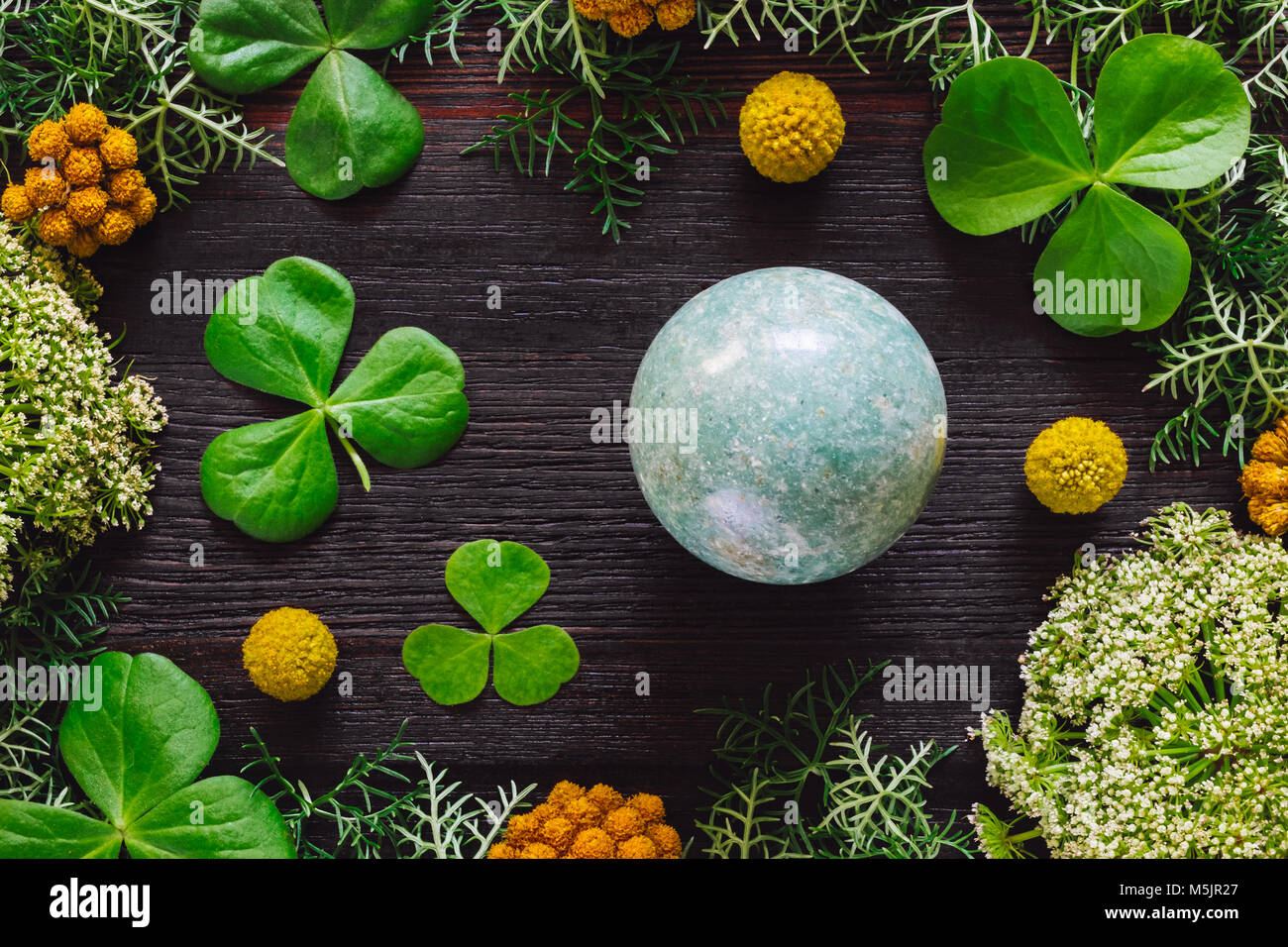 Green Aventurine Sphere with Shamrocks and Mixed Foliage on Dark Table - Stock Image