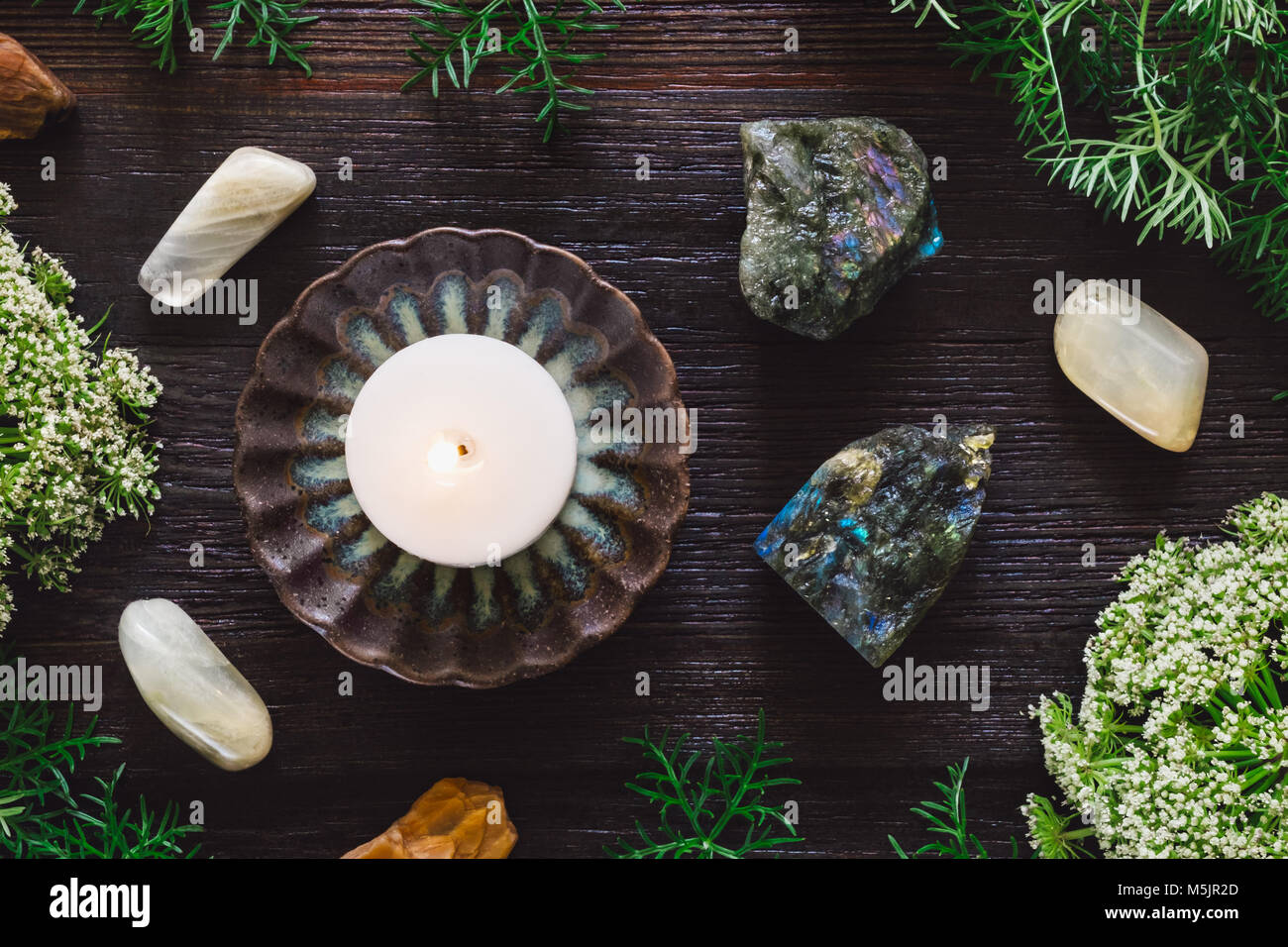 White Candle with Labradorite and Moonstone on Dark Table - Stock Image
