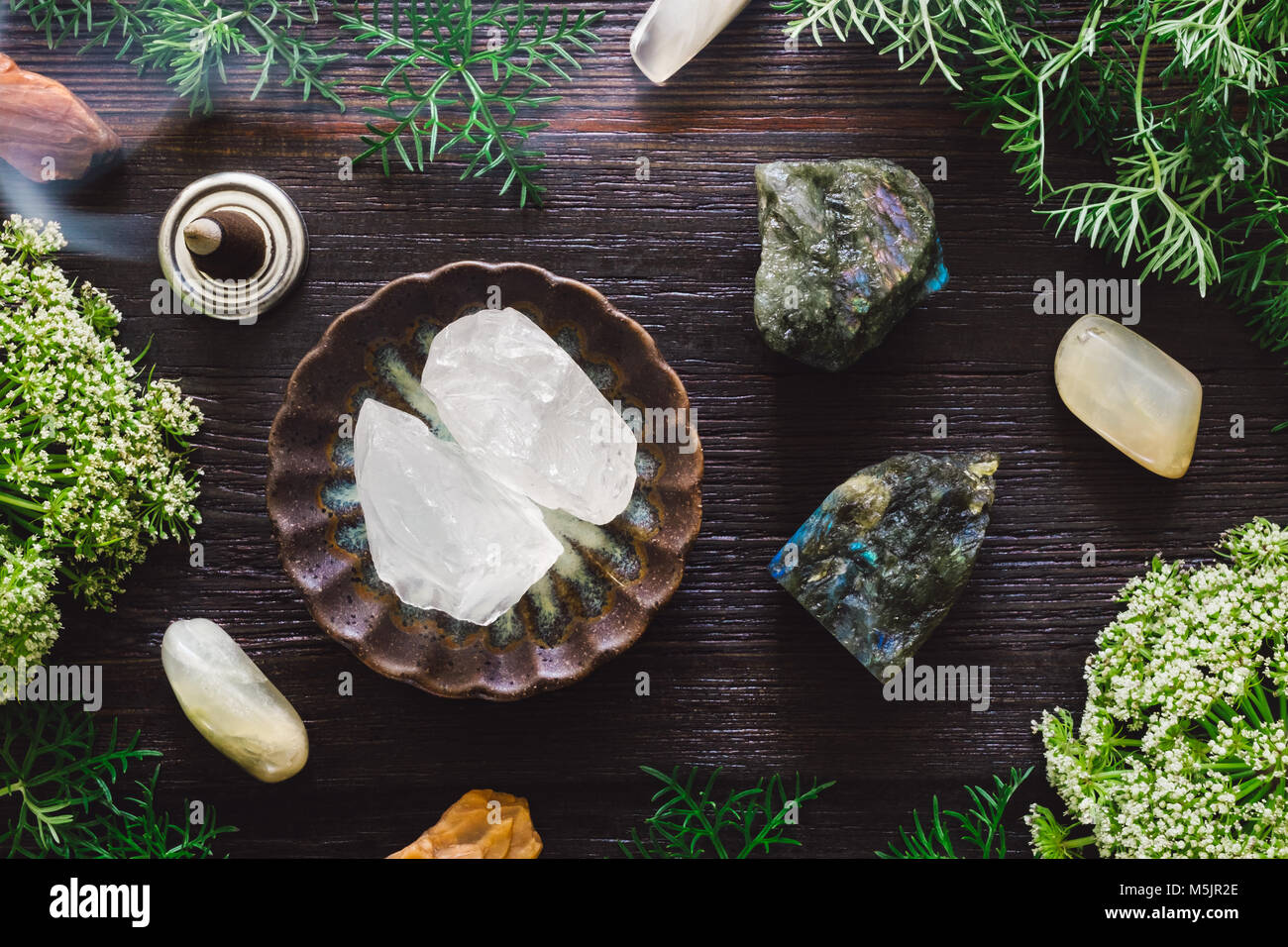 Ceramic Bowl of Girasol with Moonstone, Labradorite and Incense on Dark Table - Stock Image