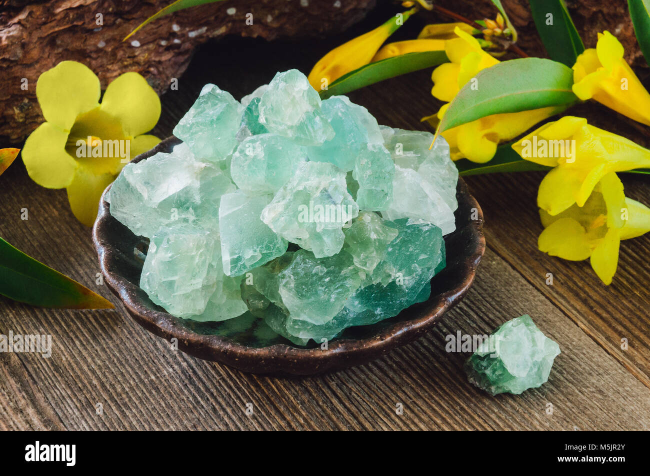 Ceramic Bowl of Rough Green Fluorite on Rustic Background - Stock Image