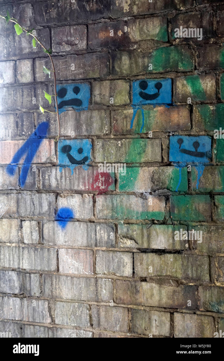 faces painted on bricks in disused wartime air raid shelter - Stock Image