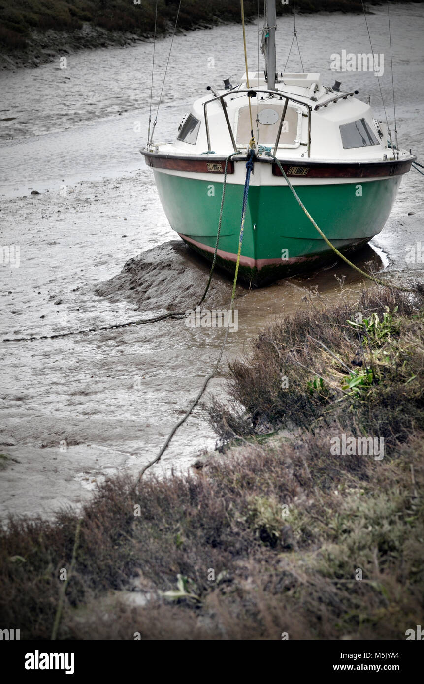 small sailing cruiser aground in mud at thornham staithe, north norfolk england - Stock Image