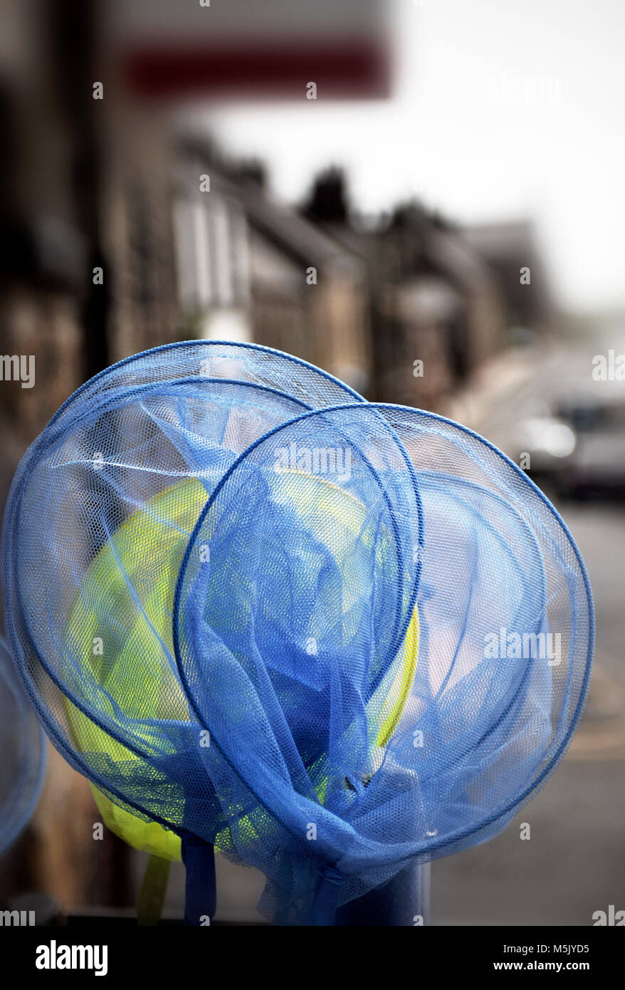 childrens fishing nets outside shop in high street - Stock Image