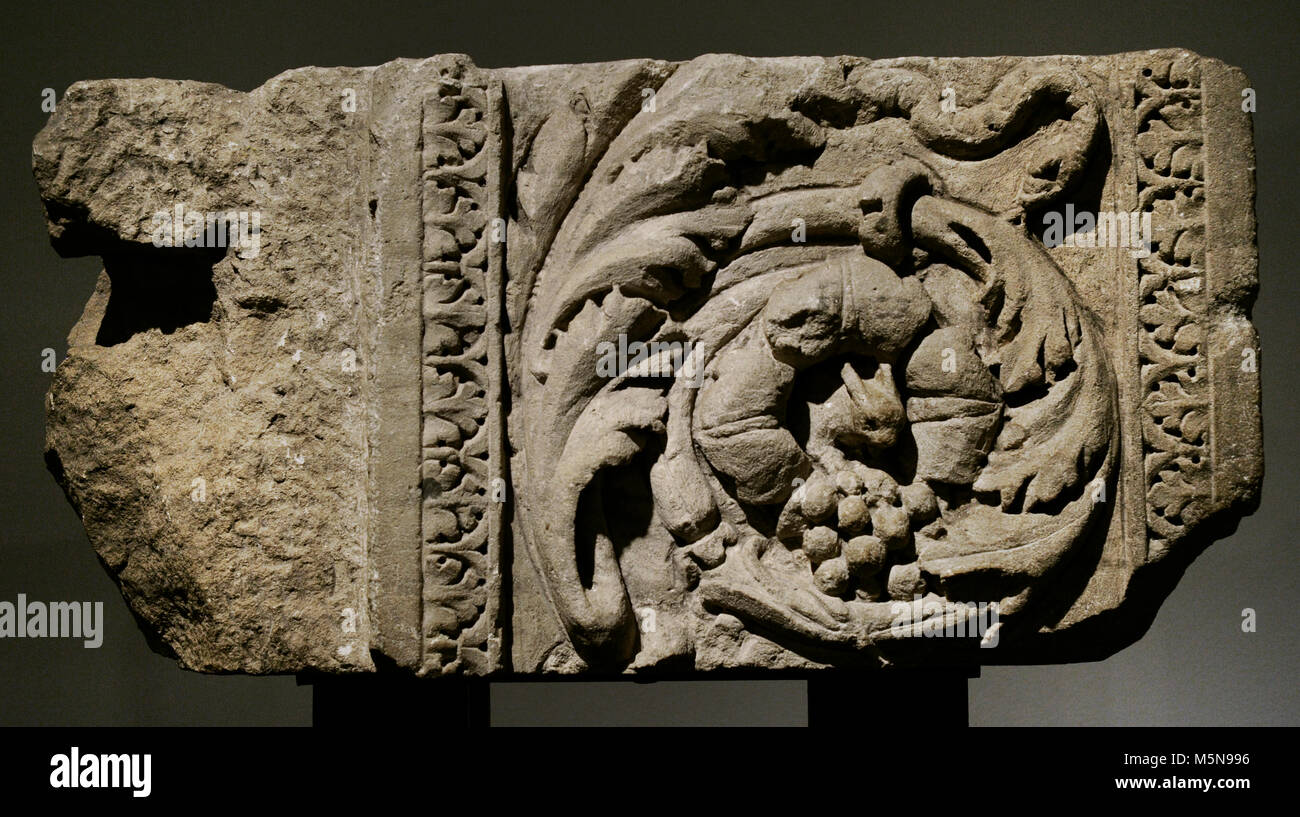 Detail of the left jamb of a monumental door decorated with acanthus leaves, a squirrel and a snake. Limestone and - Stock Image
