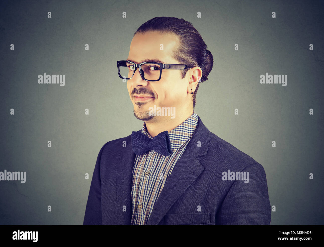 Young formal man in suit and glasses looking cannily at camera being liar. - Stock Image