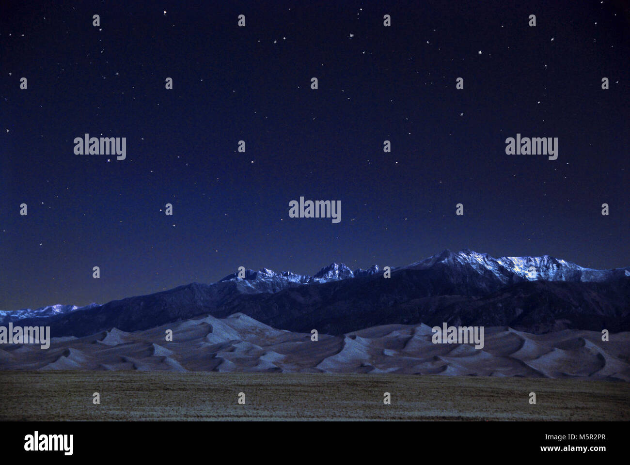 Dunes, Crestone Peaks and Stars on a Quarter Moon Night . Stock Photo