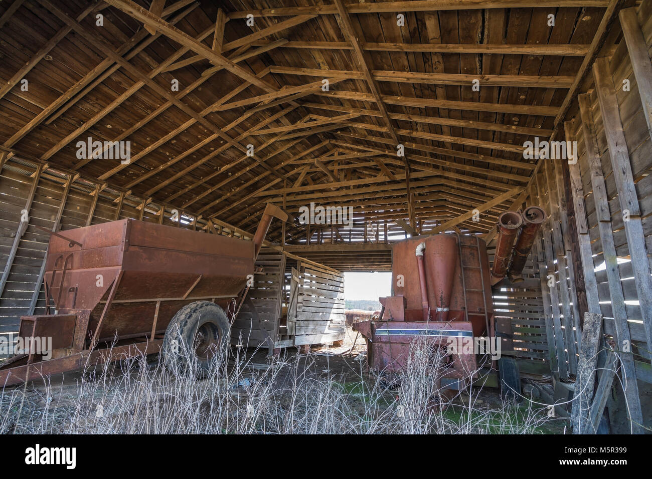 Inside of an old, open air barn. Stored inside is old agricultural equipment. - Stock Image