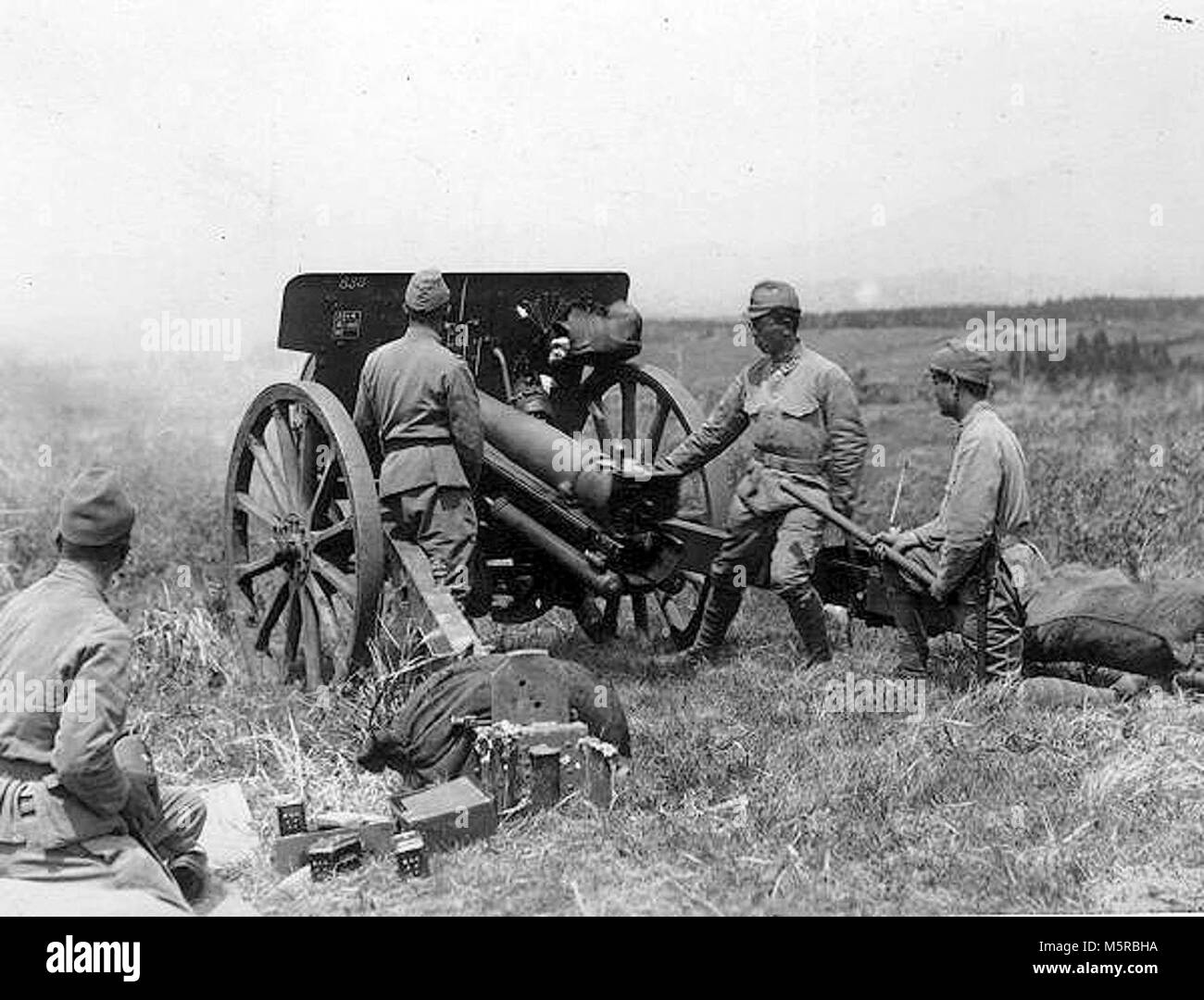 Cadets of the Imperial Japanese Army during shooting training with Type 91 10-cm-howitzer (with wooden spoked wheels) - Stock Image