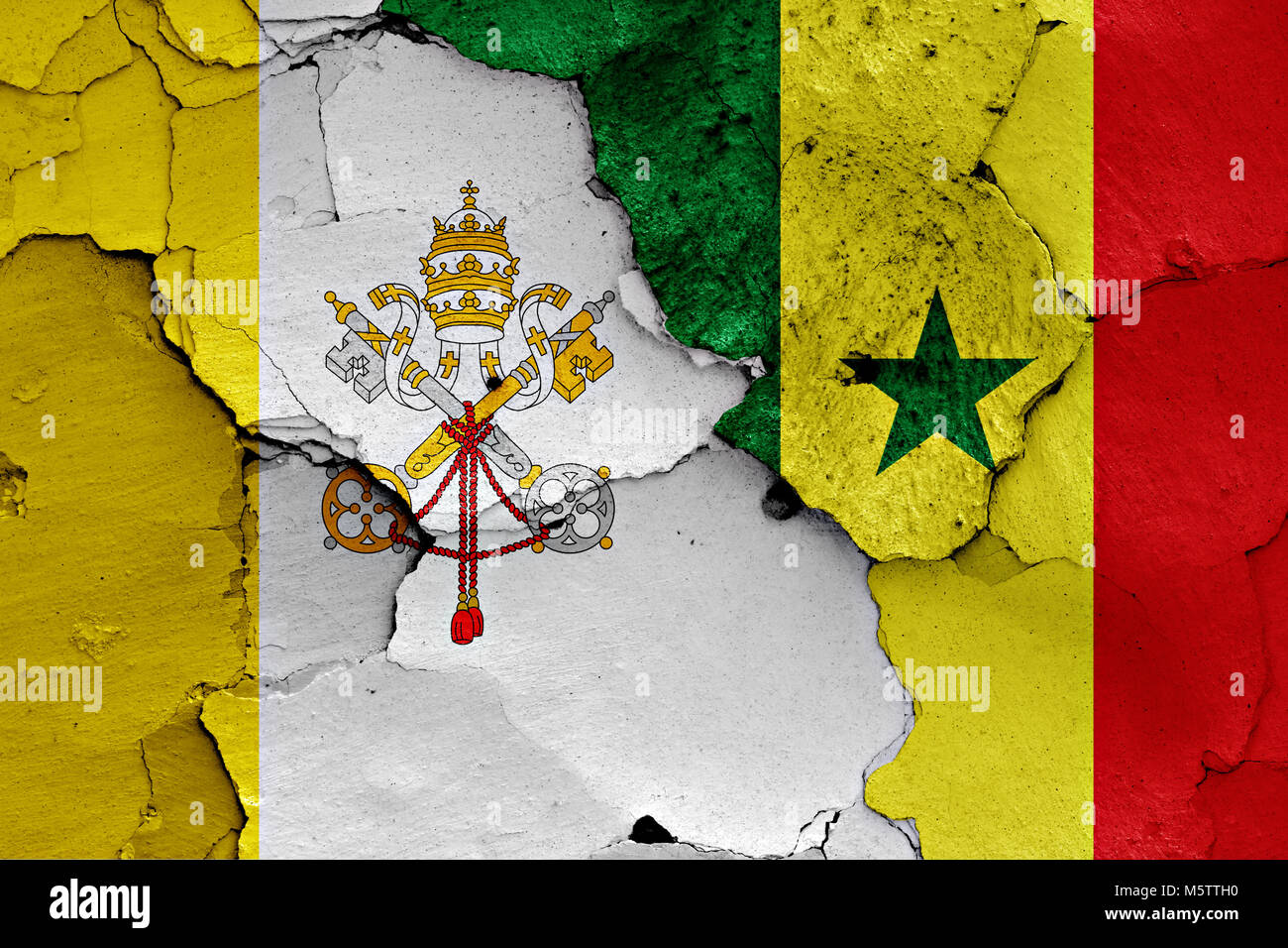 flag of Vatican and Senegal painted on cracked wall - Stock Image