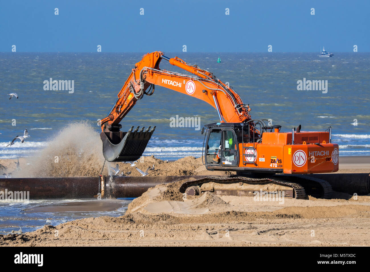 Hydraulic excavator connecting pipes of pipeline during sand replenishment / beach nourishment works along the Belgian - Stock Image