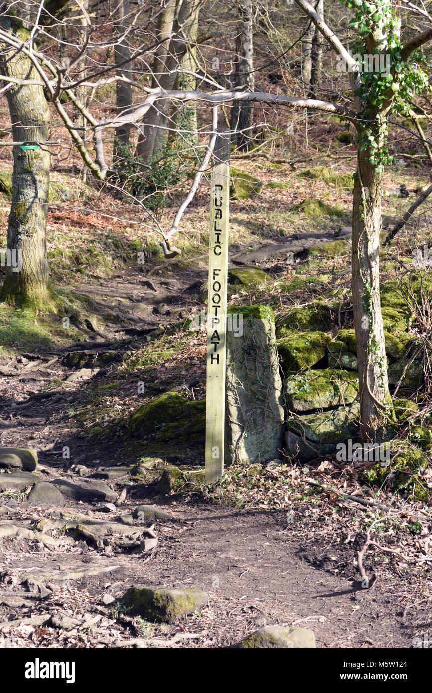 Sign saying Public Footpath on a path through woodland below Froggatt Edge. Froggatt, Derbyshire, UK. - Stock Image