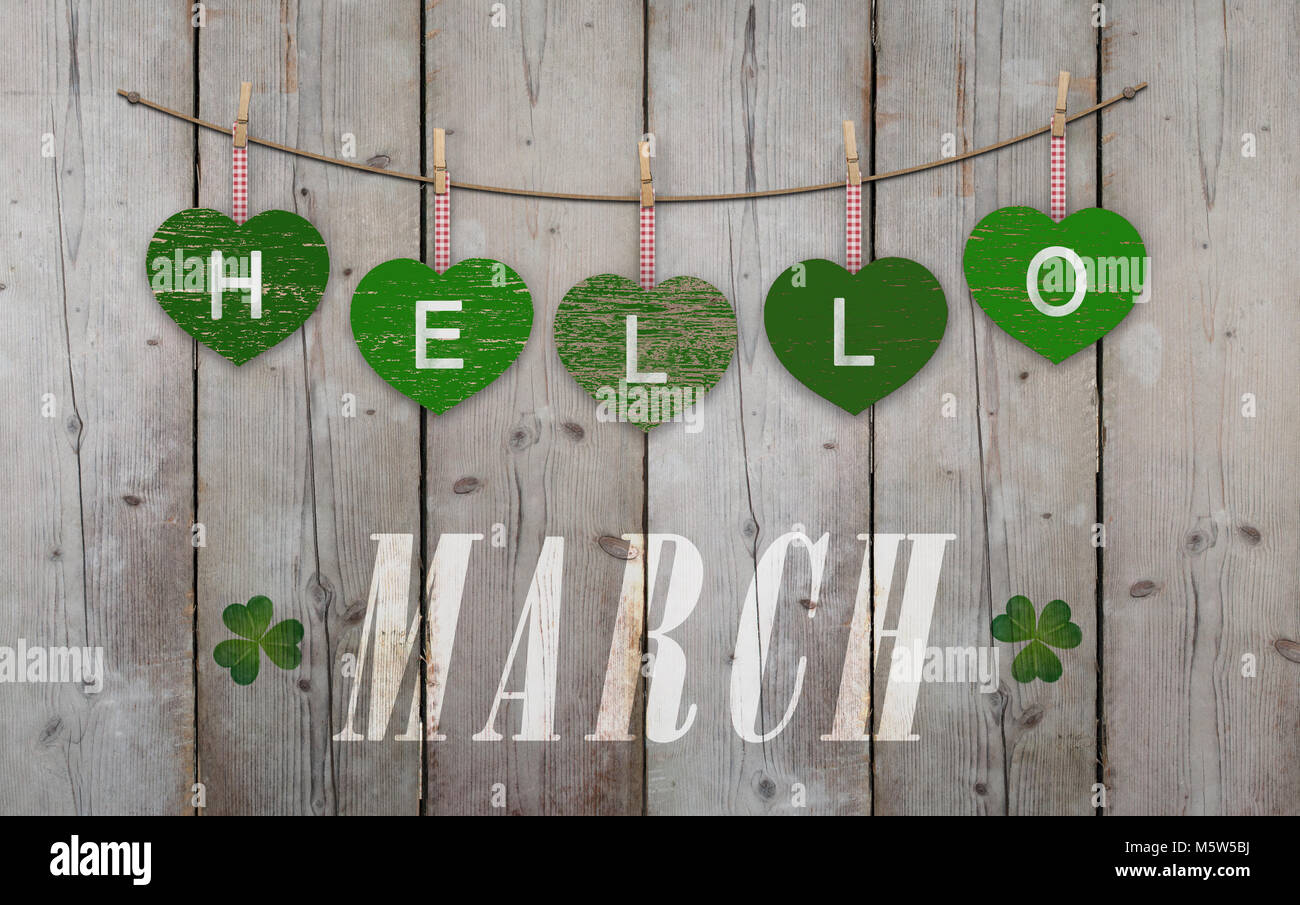 Hello March written on hanging green hearts and weathered wooden background, with clover - Stock Image