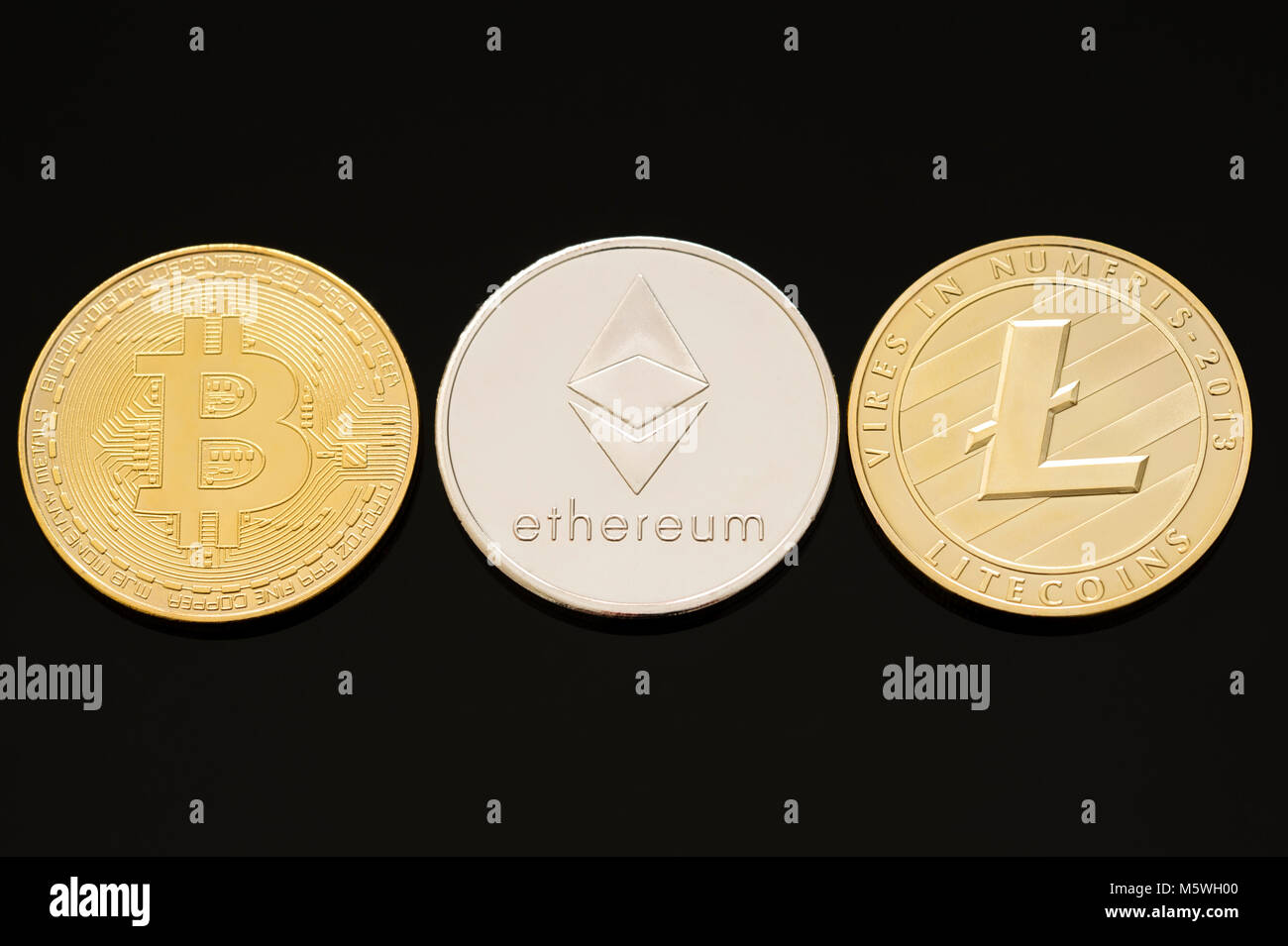 A collection of the three most popular digital or cryptocurrencies. Bitcoin, Ethereum (Ether) & Litecoin on - Stock Image