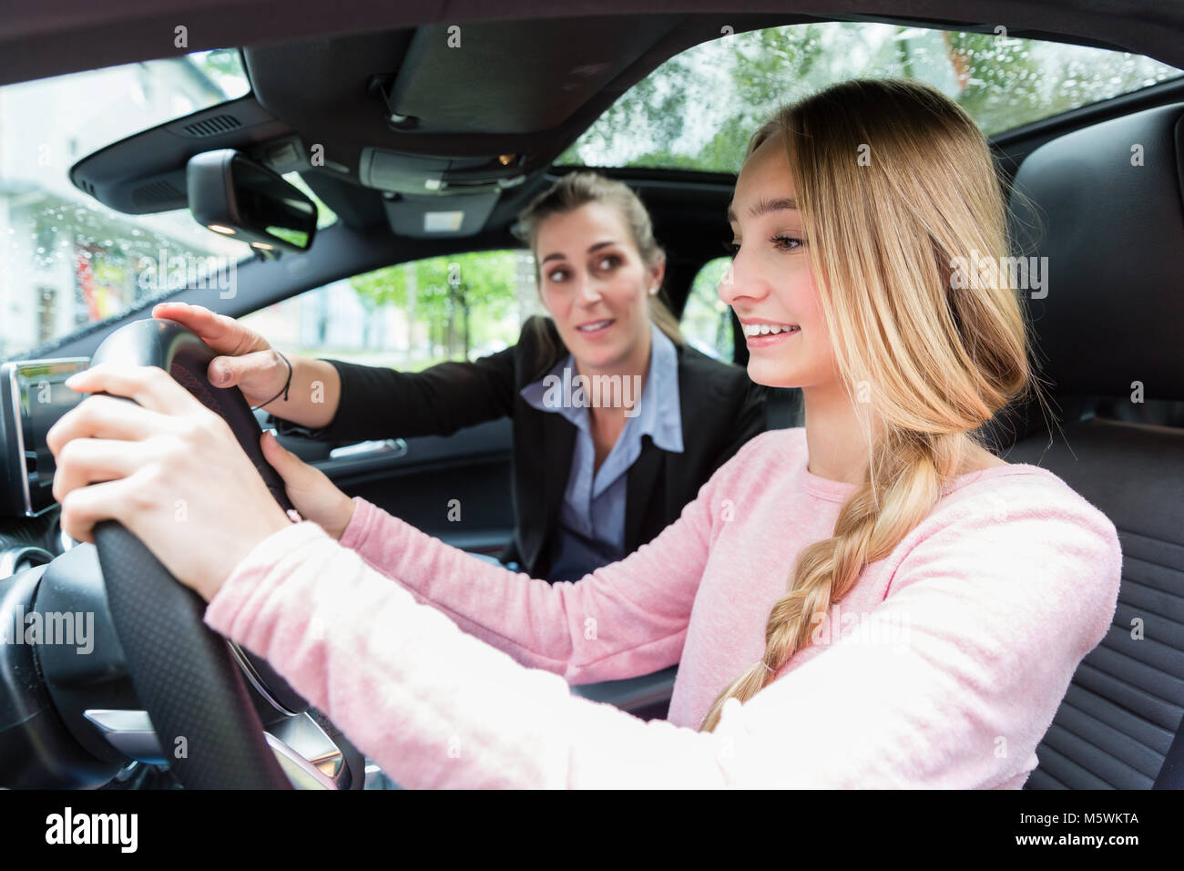 Student on wheel of car in driving lesson with her teacher - Stock Image