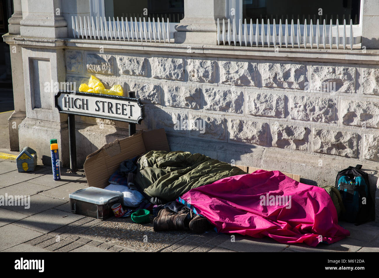 Windsor, UK. 27th February, 2018. A homeless person sleeps in the High Street opposite Windsor Castle after a night Stock Photo