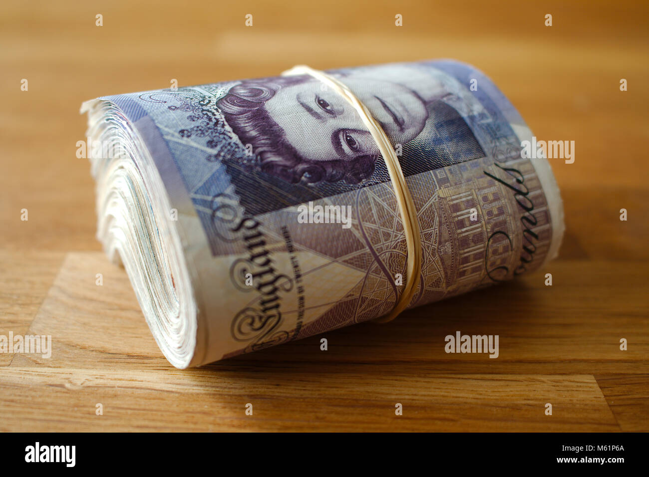 A rolled up bunch of bank notes, giving the impression of wealth. Stock Photo