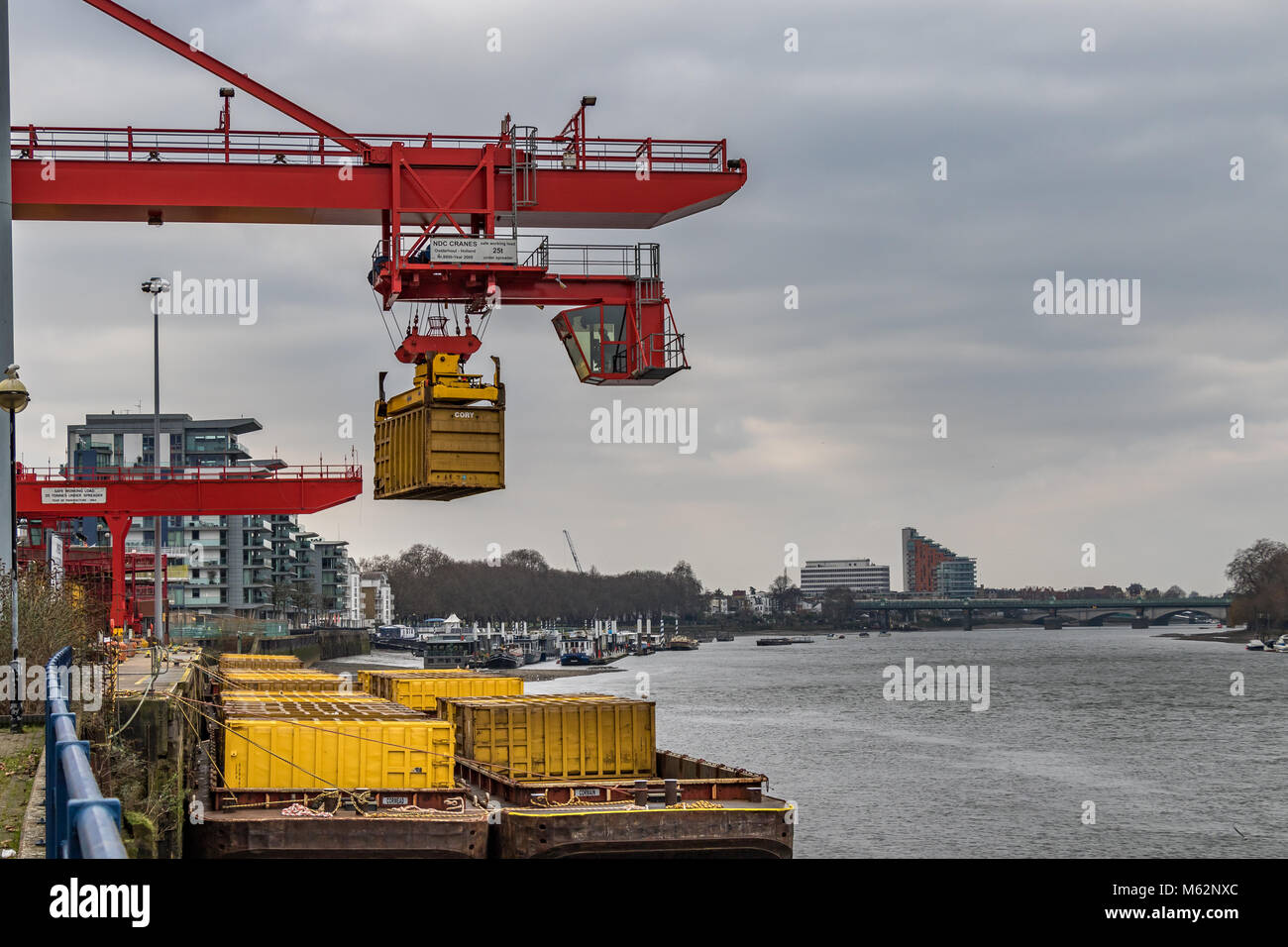 A container handling crane at Western Riverside Waster Authority near Wandsworth Bridge, places a container of domestic - Stock Image