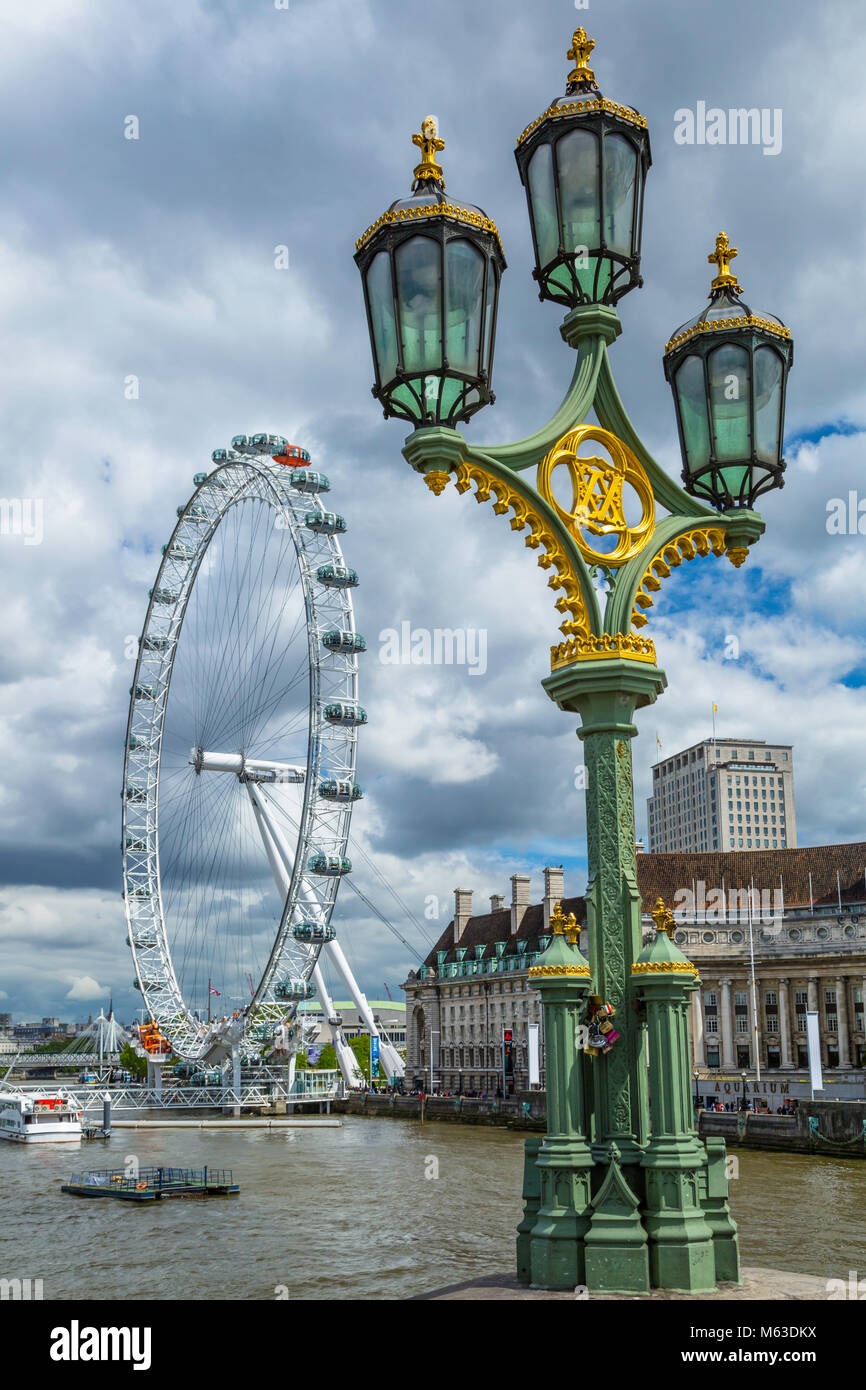Street lamps on Westminster Bridge and the London Eye. Stock Photo
