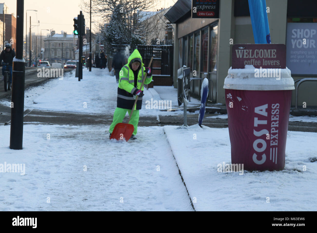 LONDON, UK - February 28: A worker spades snow off a walkway as streets of East London were covered with snow following - Stock Image