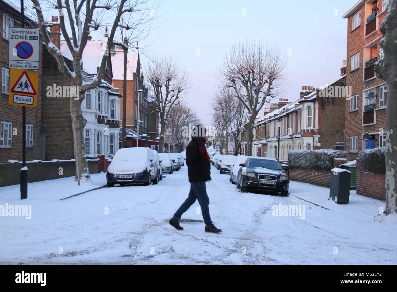London, UK. 28th Feb, 2018. UK Weather: A man seen walking across Snadringhan Road as streets of East London were - Stock Image