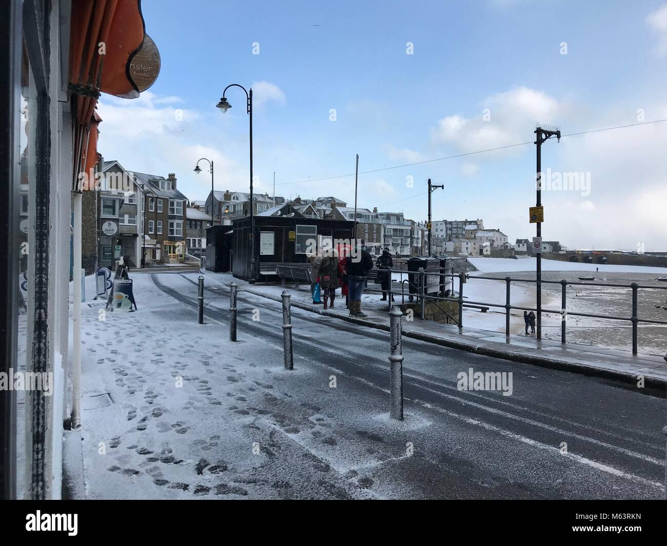 Cornwall, UK. 28th February, 2018. People walk across the harbour front of St Ives, Cornwall in snow storm. Credit: - Stock Image