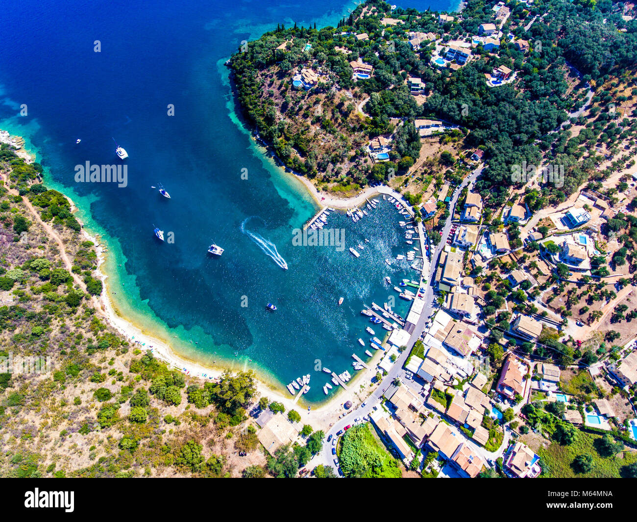 Agios Stefanos bay, one of the most beautiful fishing villages in Corfu Island. Kerkyra, Greece. Aerial view. Stock Photo