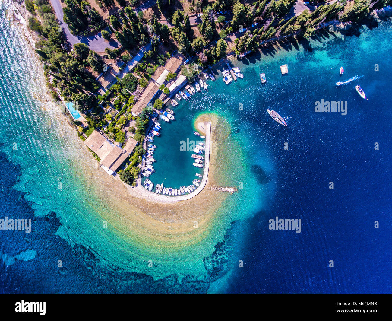 Kouloura old fishing village and beach. Corfu (Kerkyra) Island, Greece, Europe. Fishing boats and clear blue waters. - Stock Image