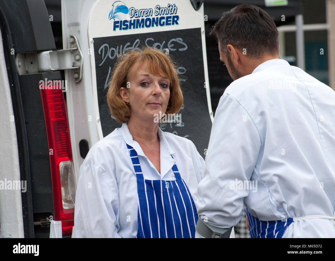 Woman in white coat and striped apron looks quizzically at the camera - Stock Image
