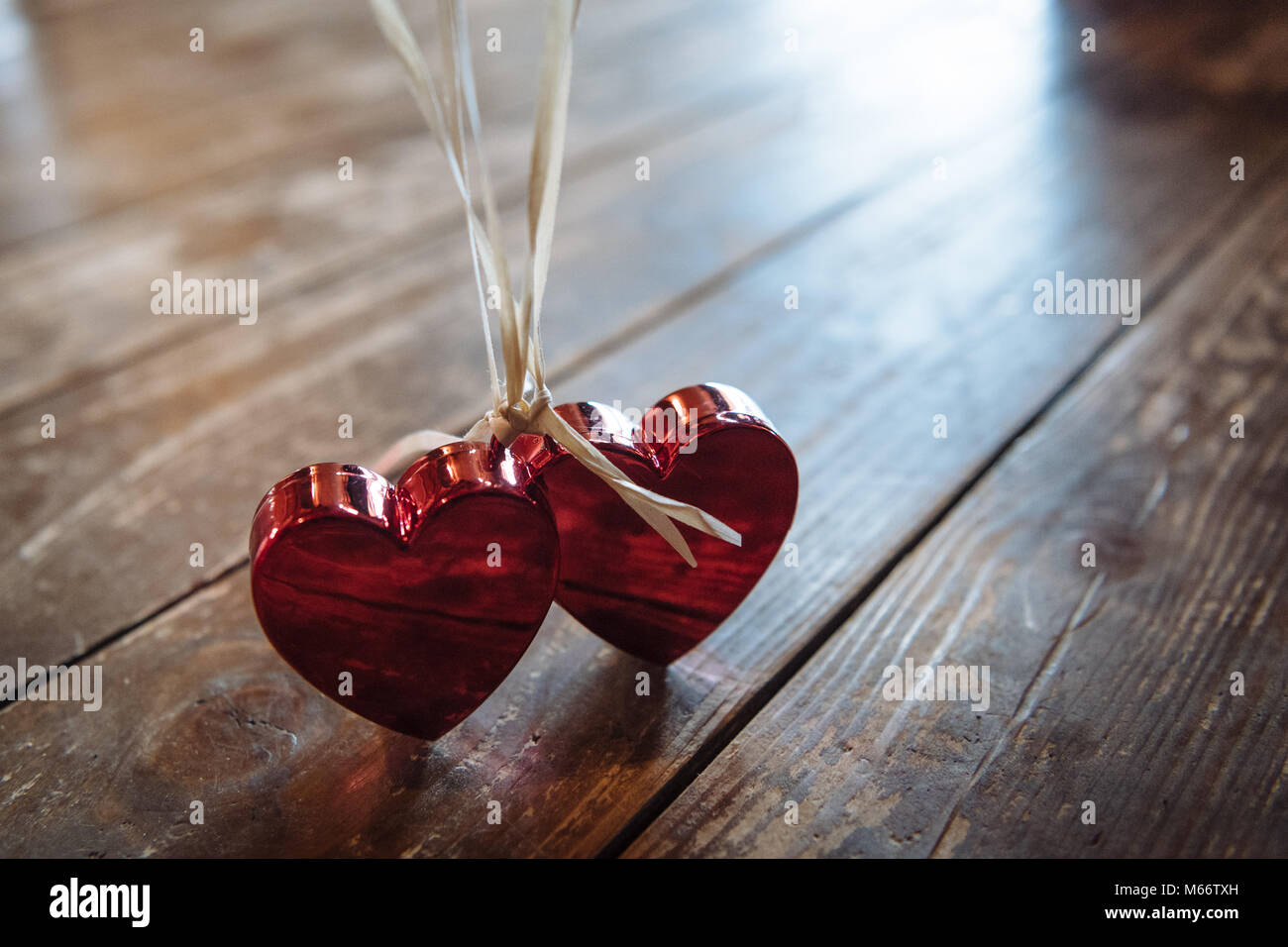 Symbol picture love, wedding, partnership, Two red hearts on white strings - Stock Image