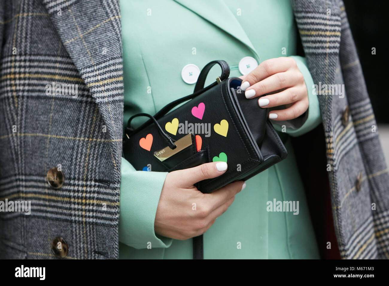 983a72f2e1ec MILAN - FEBRUARY 25  Woman with black leather Loewe bag with colorful hearts  and pastel green jacket before Emporio Armani fashion show