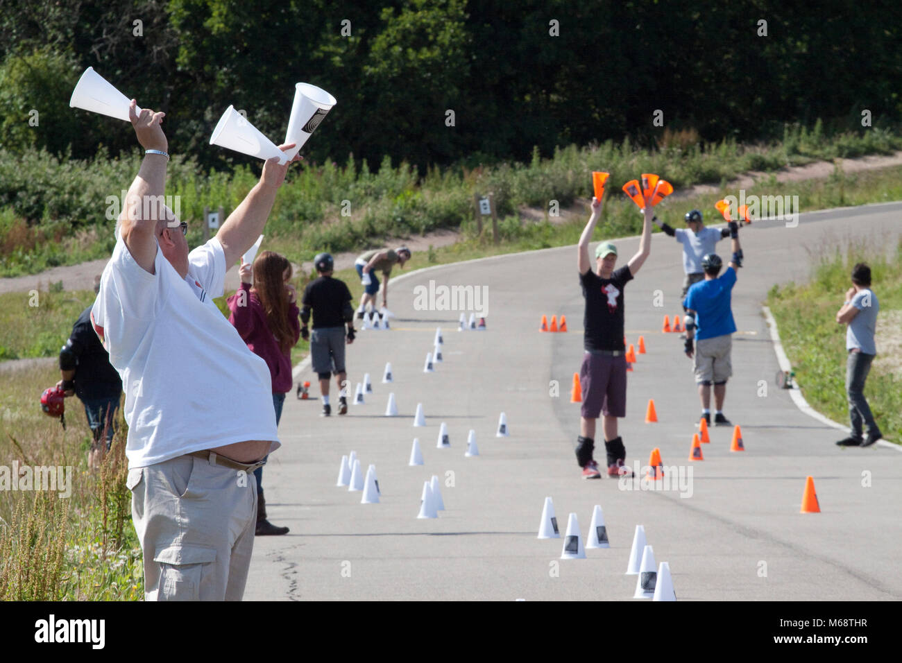 Competitors and helpers hold up touched cones at a skateboard slalom - Stock Image