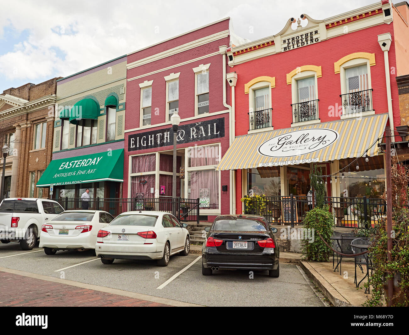 Small quaint shops with fancy storefronts in small town America line the street in Opelika Alabama, USA. - Stock Image