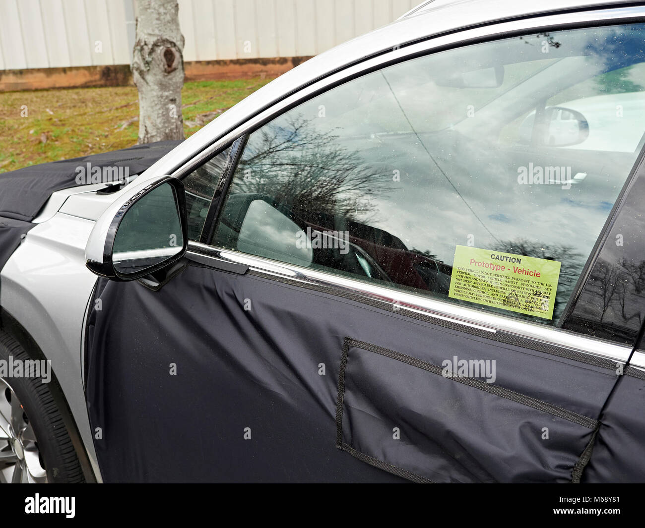 Prototype Hyundai SUV automobile or car disguised in a black vinyl  camouflaged wrap parked in a parking lot in - Stock Image