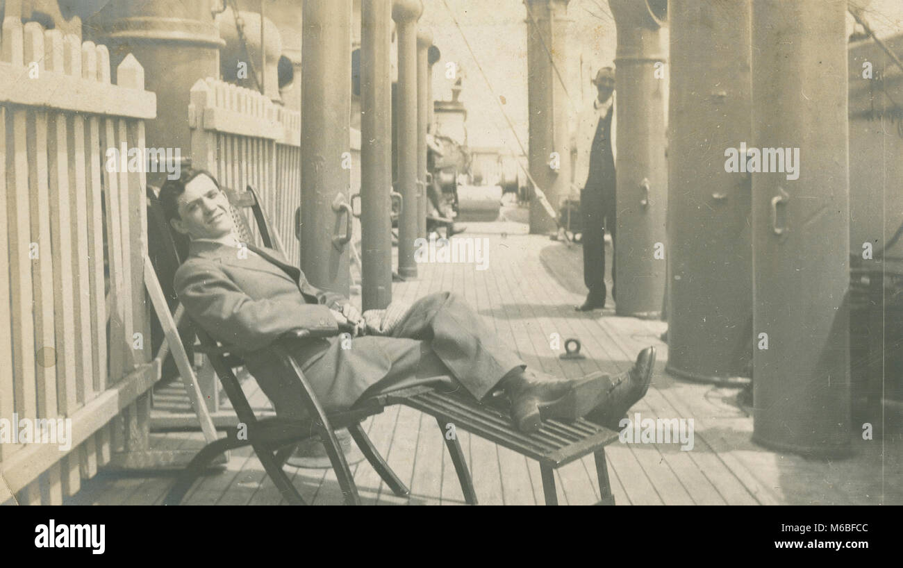 Antique c1900 photograph, man reclining on deck chair aboard a steamship. - Stock Image