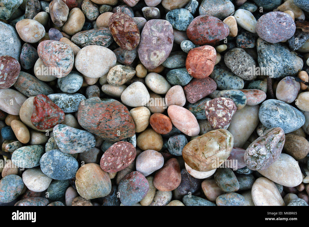 A close up view of colorful pebbles on Lochinver Beach along the west coast of Scotland. - Stock Image
