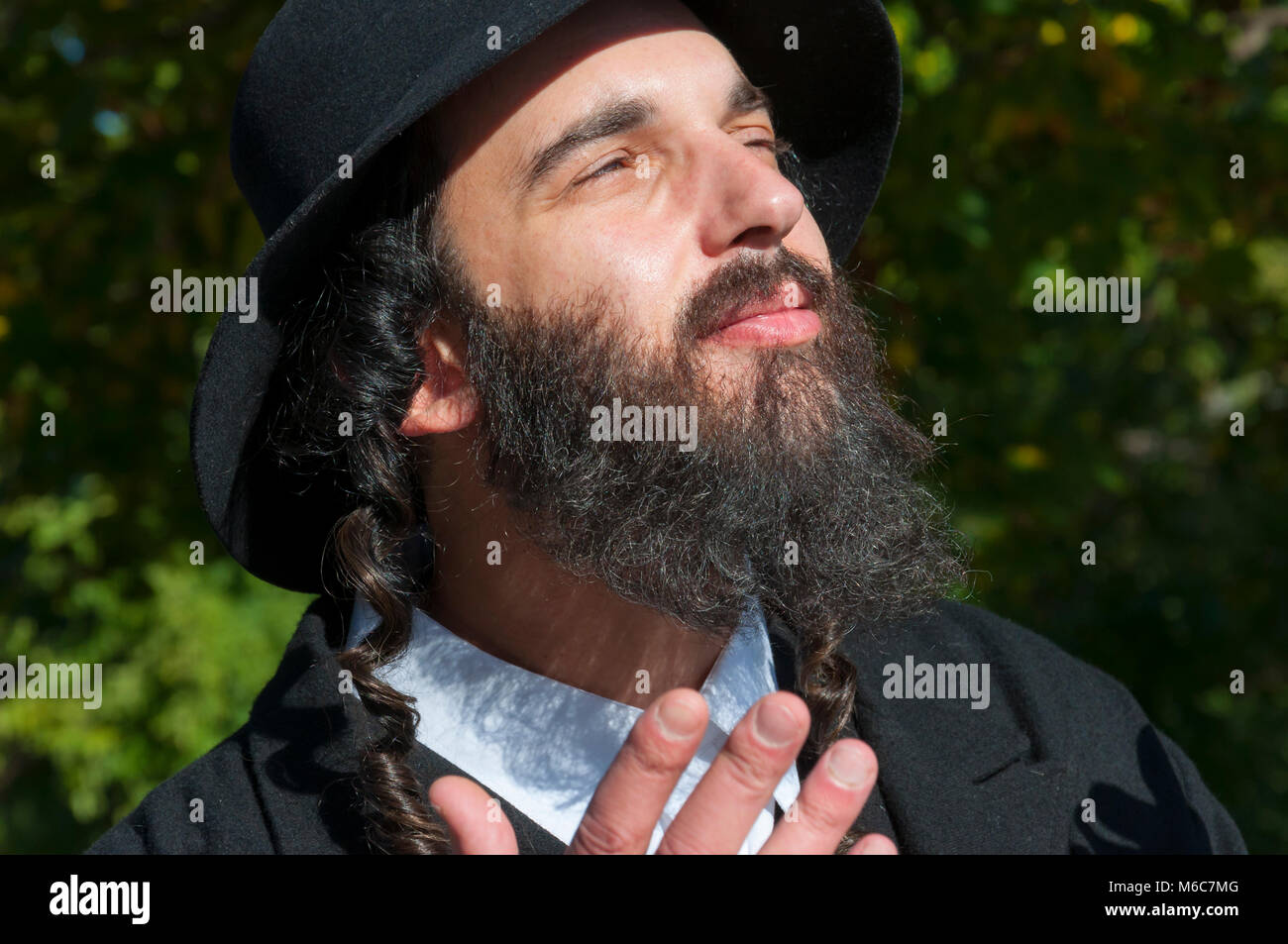 1422e3a9c75 Outdoor sunny portrait of a young happy praying traditional orthodox Jewish  man with eyeglasses and black beard