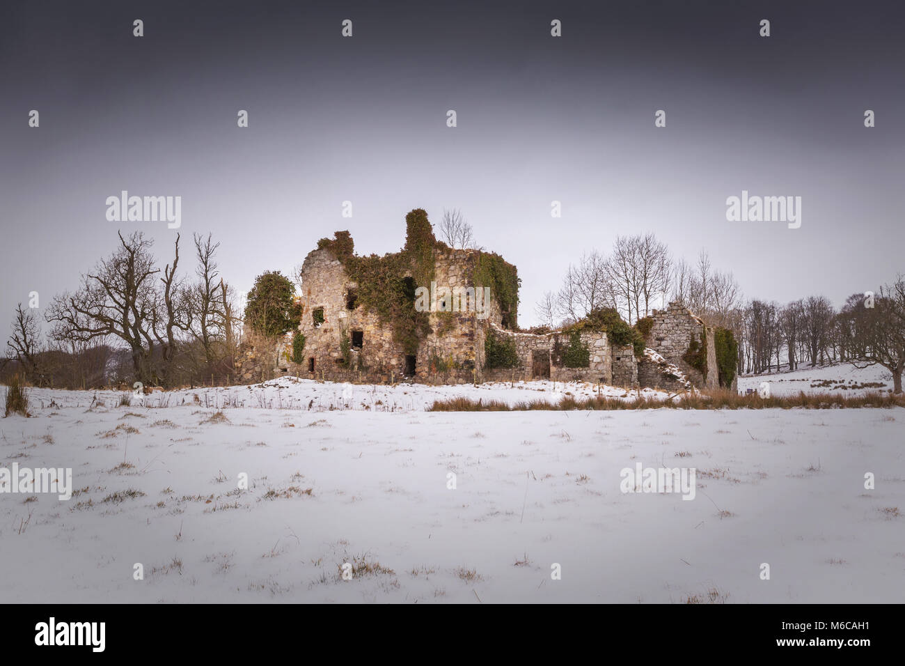 The ruins of haunted Gight Castle at Braes of Gight near Methlick, Aberdeenshire, Scotland, in the snow during winter - Stock Image