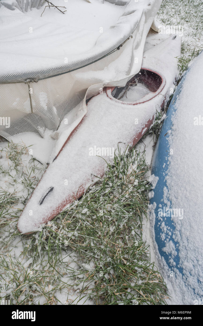 Snow covered canoe laid up on the banks of the River Fowey at Lostwithiel. During the 2018 'Beast from the East' - Stock Image