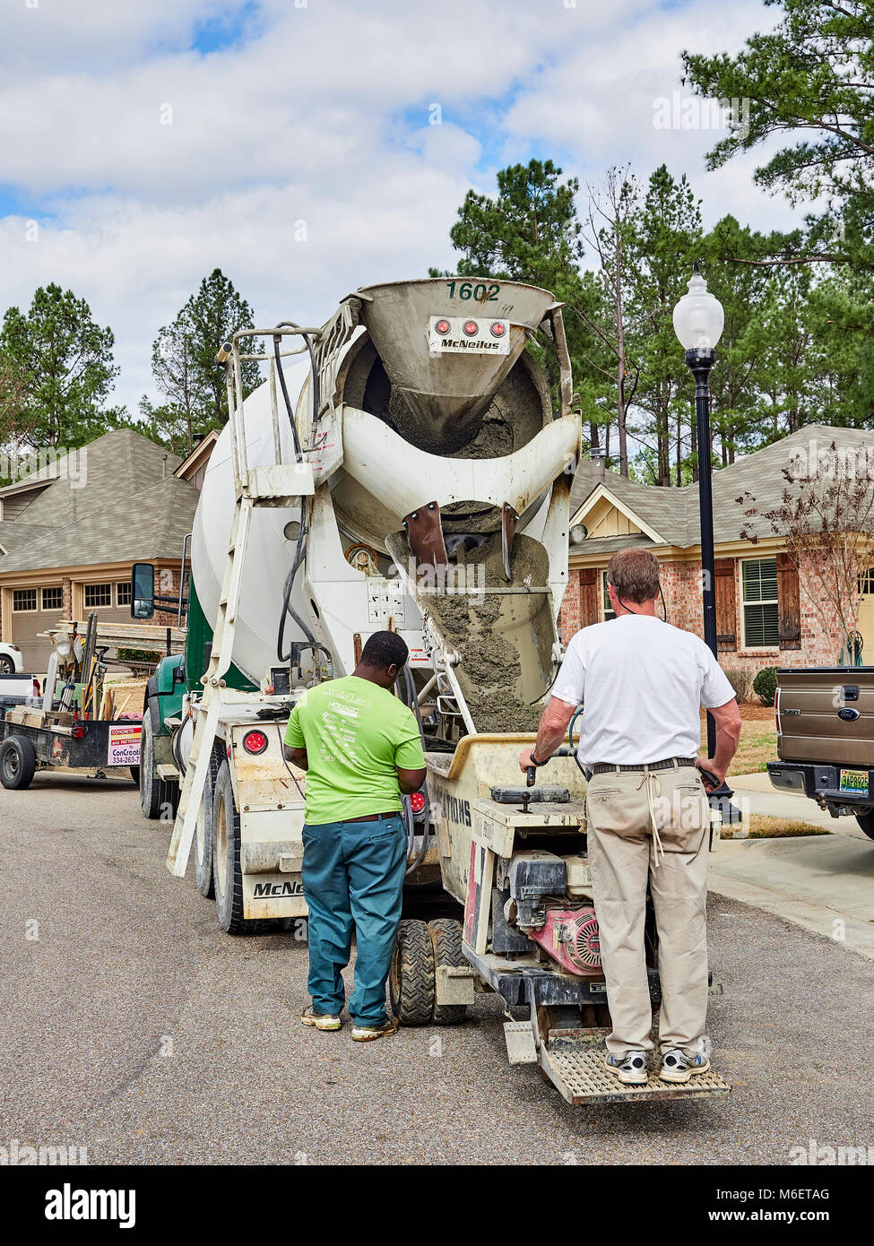 Hodgson concrete truck delivering concrete to a residential construction job with two workers loading the cement - Stock Image
