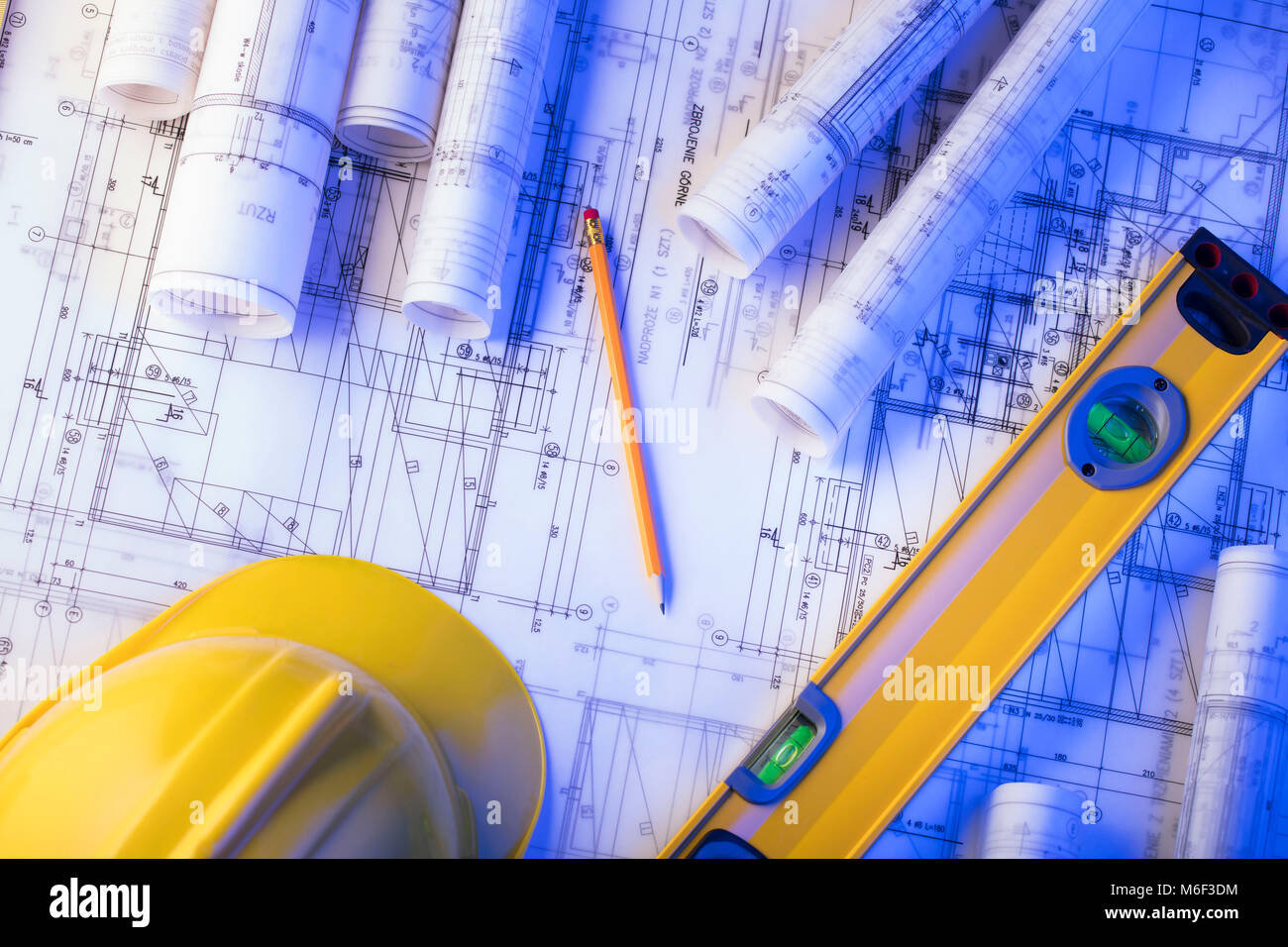 Architecture and construction concept. Rolls of blueprints, libela and helmet of constructor. - Stock Image