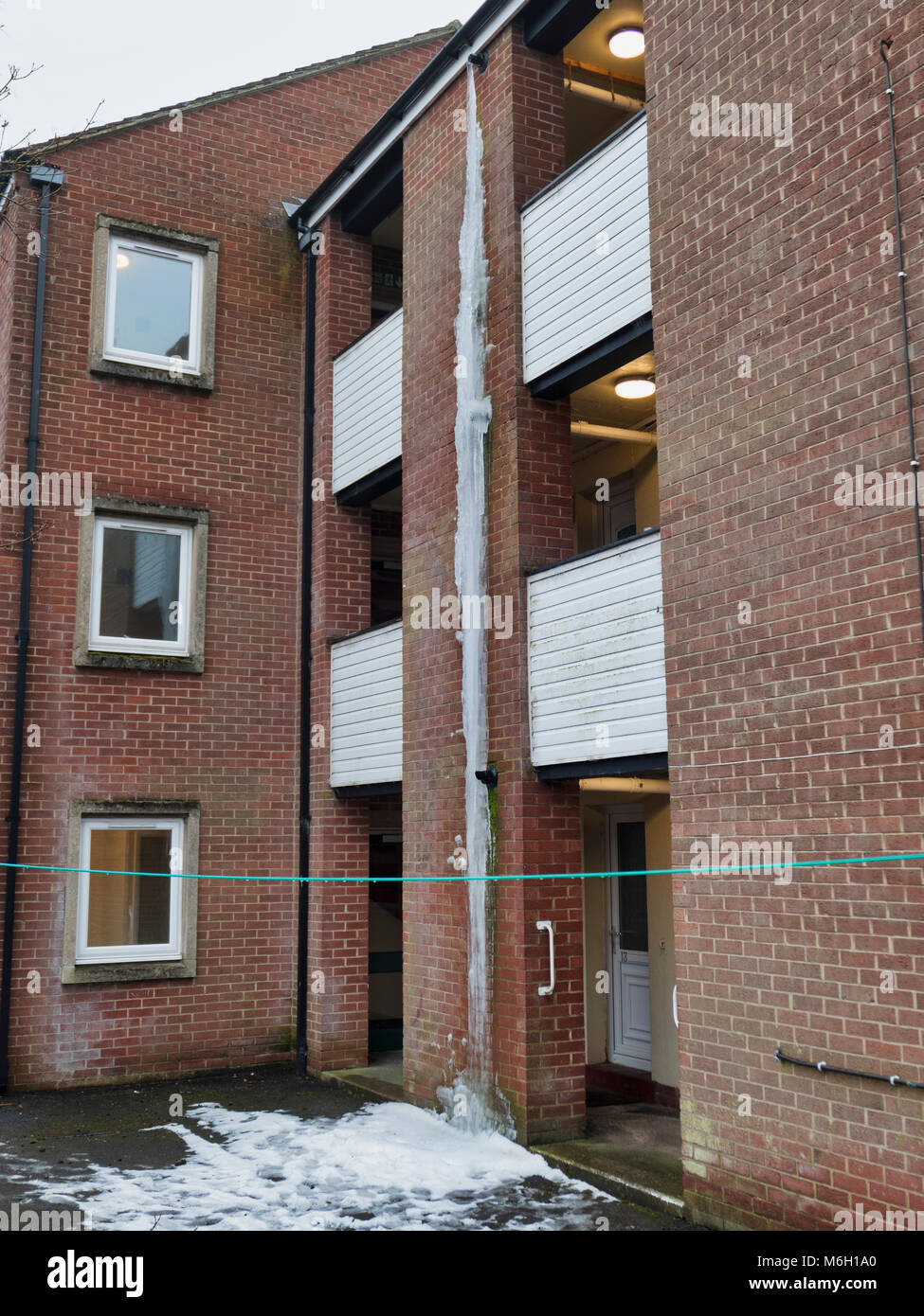 UK Weather: Gigantic 3 storey (over 20 foot) icicle formed form a frozen gas boiler exhaust pipe on a block of flats - Stock Image