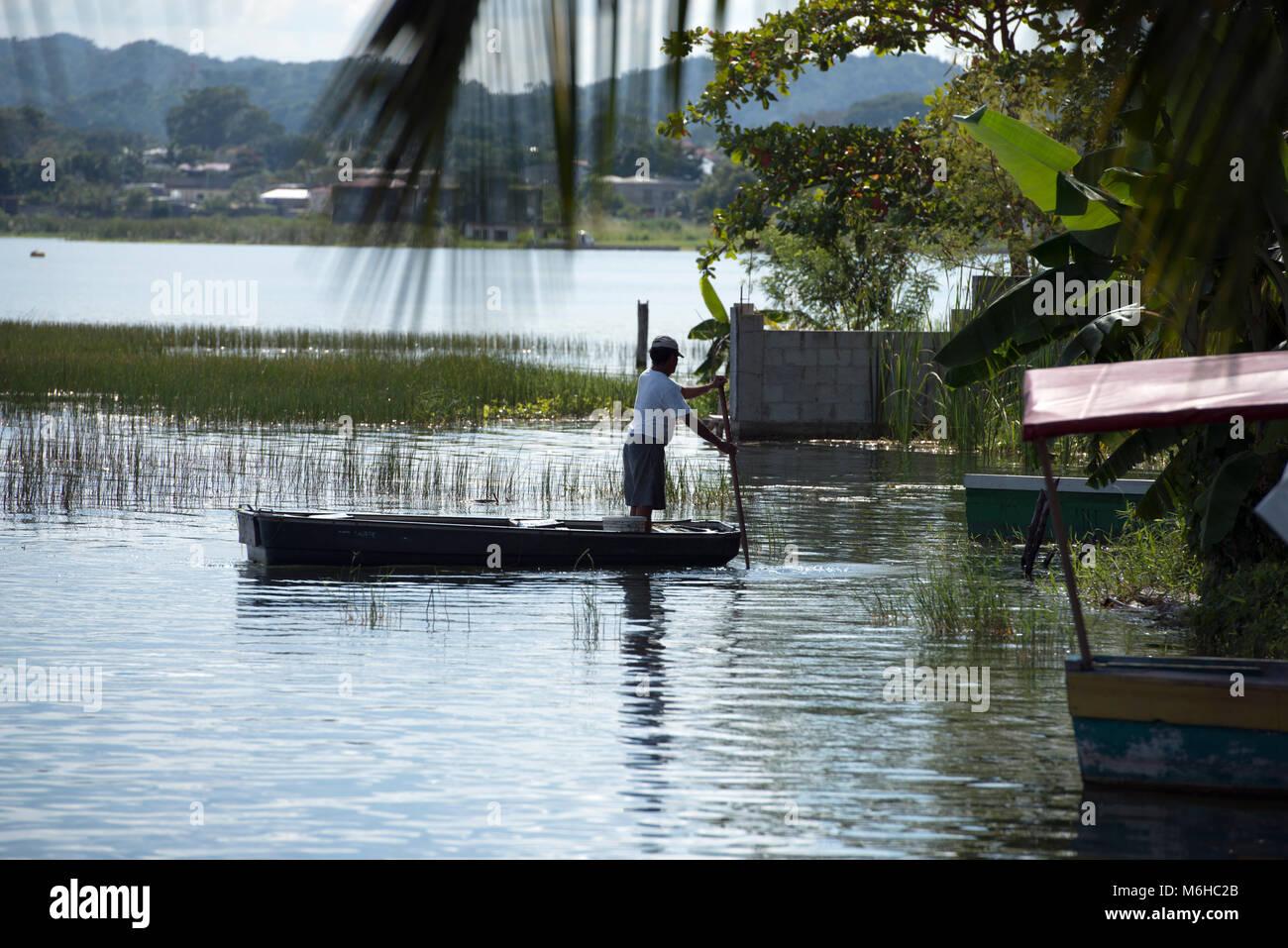 An indigenous, ethnic Itza Maya man in a boat making a living from fishing on Lake Peten, Guatemala. - Stock Image