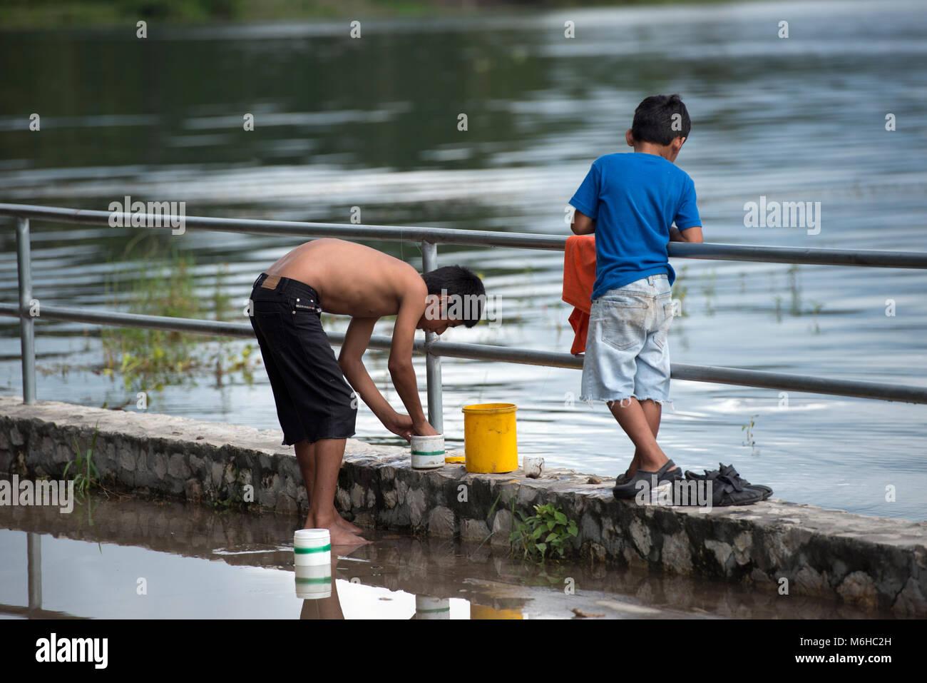 Two young, indigenous, ethnic Itza Maya boys fishing on Lake Peten, Guatemala. - Stock Image