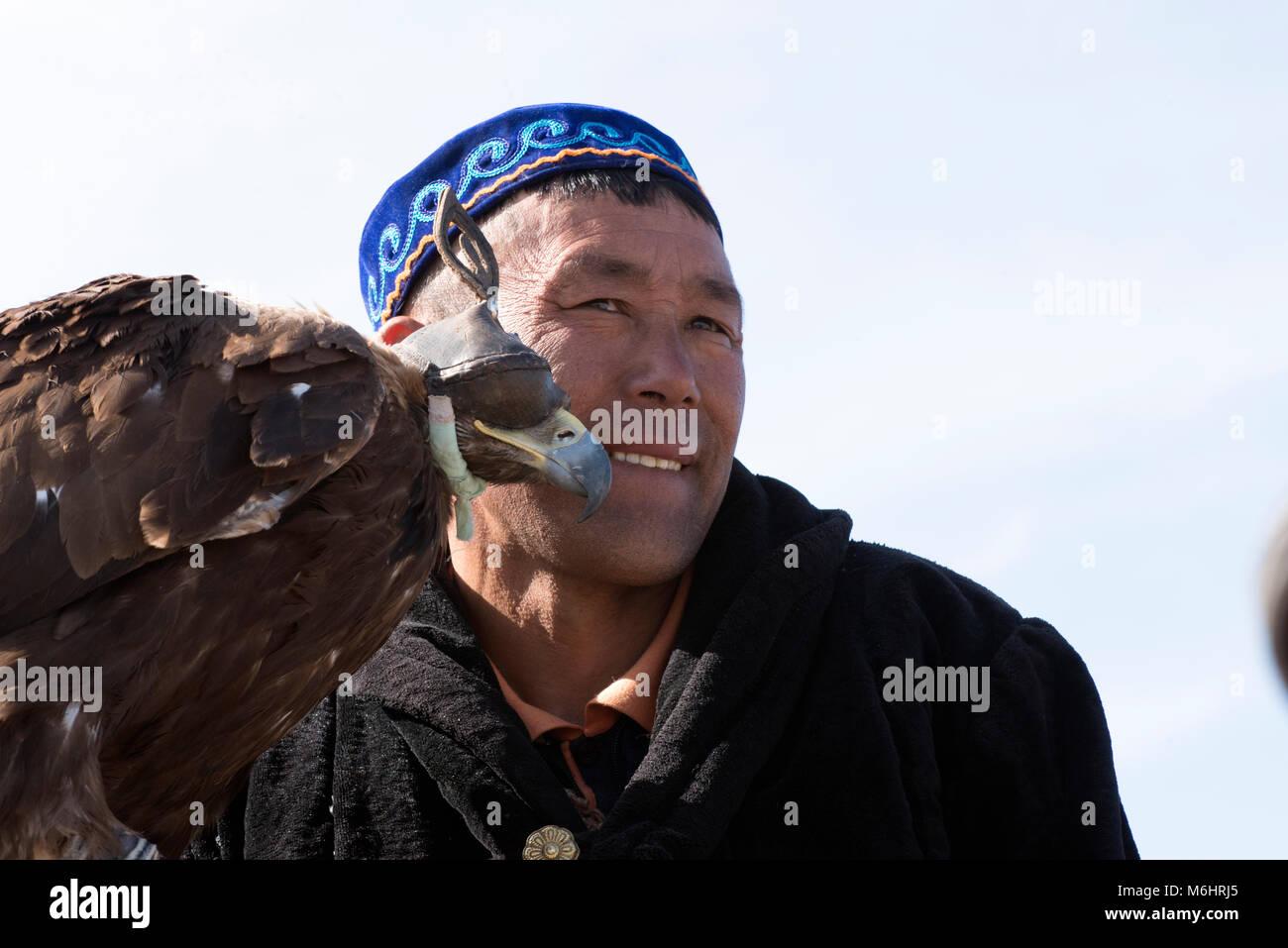 A Kazakh eagle hunter with his golden eagle at the 2017 golden eagle festival, Olgii, western Mongolia. - Stock Image