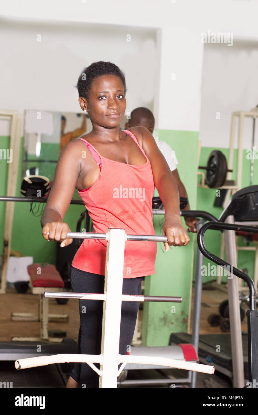 Young woman doing sports exercises in a gym to have a healthy health. - Stock Image