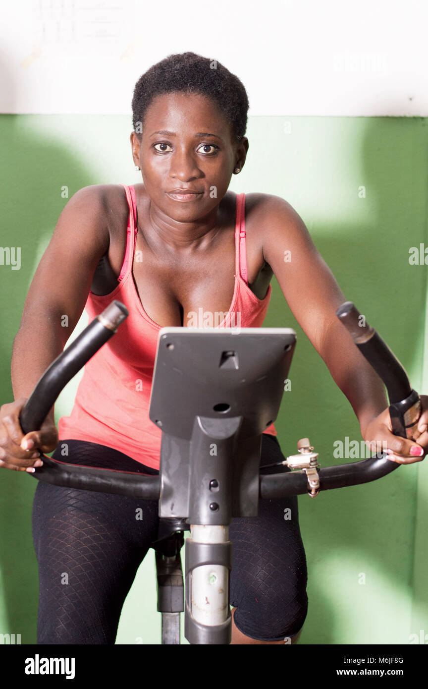 Young woman working on exercise bike  in the gym to get fit. - Stock Image