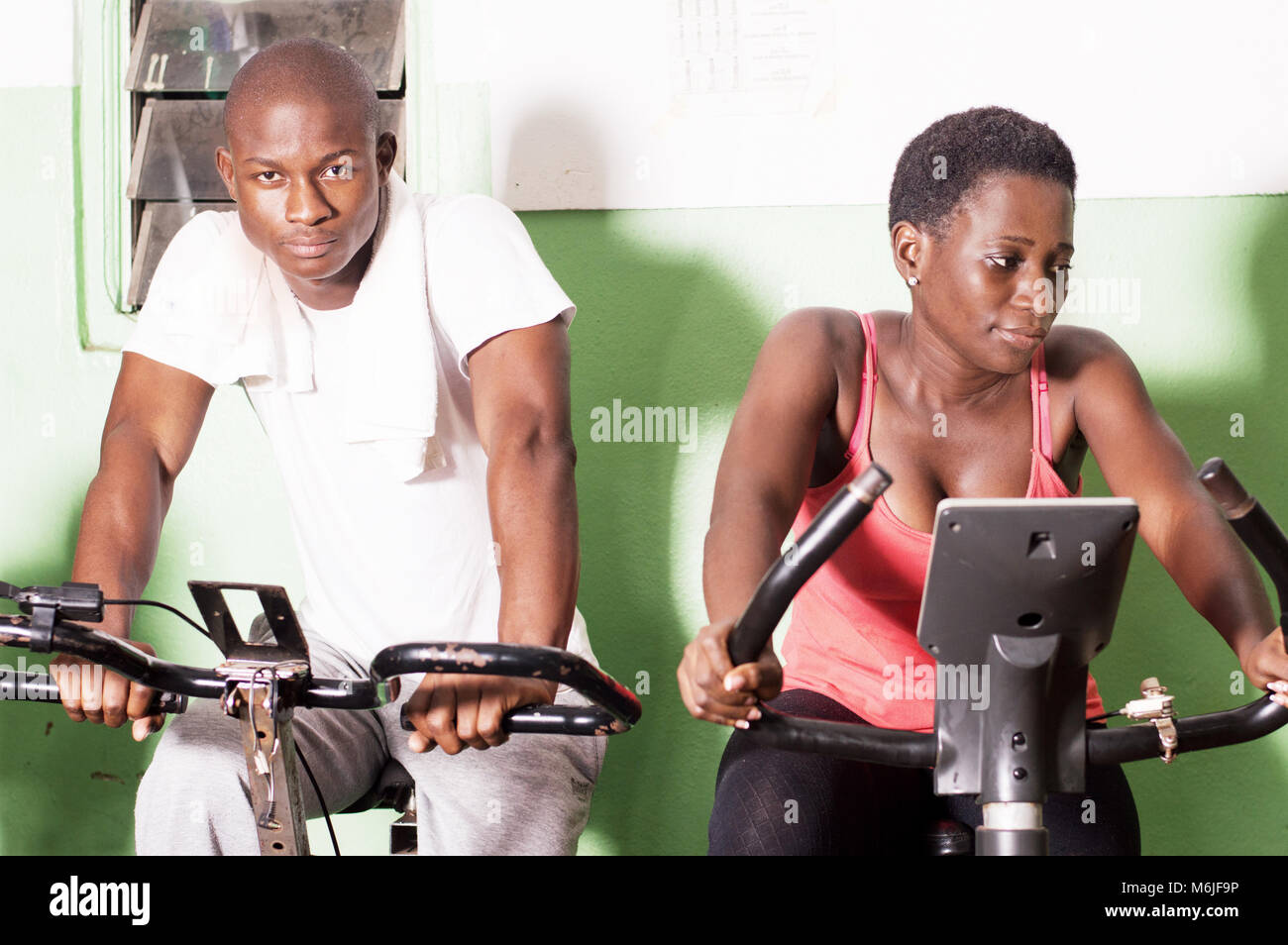 Young people working on exercise bikes in the gym to get fit. - Stock Image