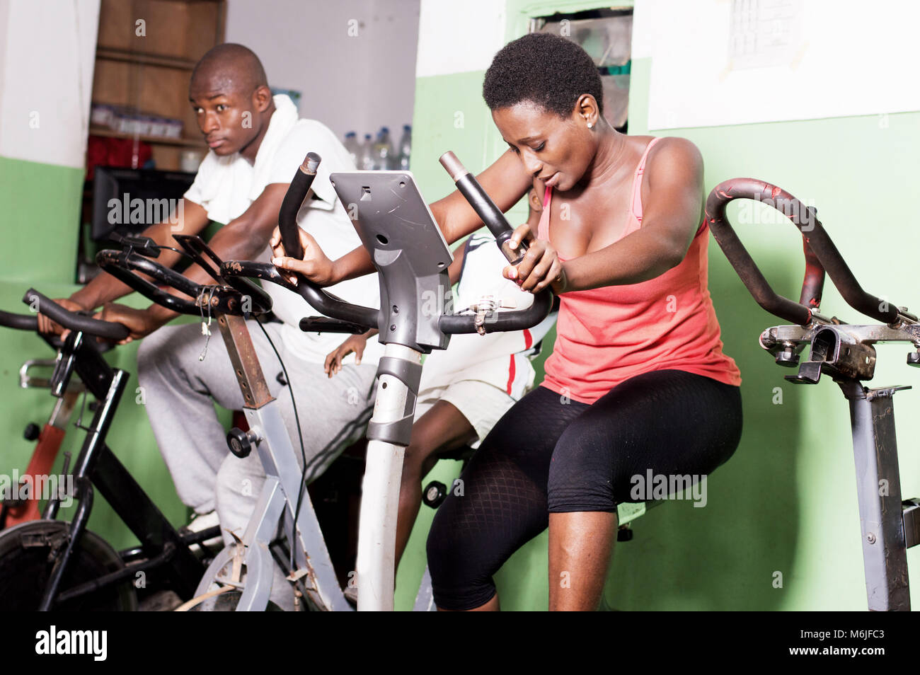Young people pedaling gymnasium bikes indoors. - Stock Image