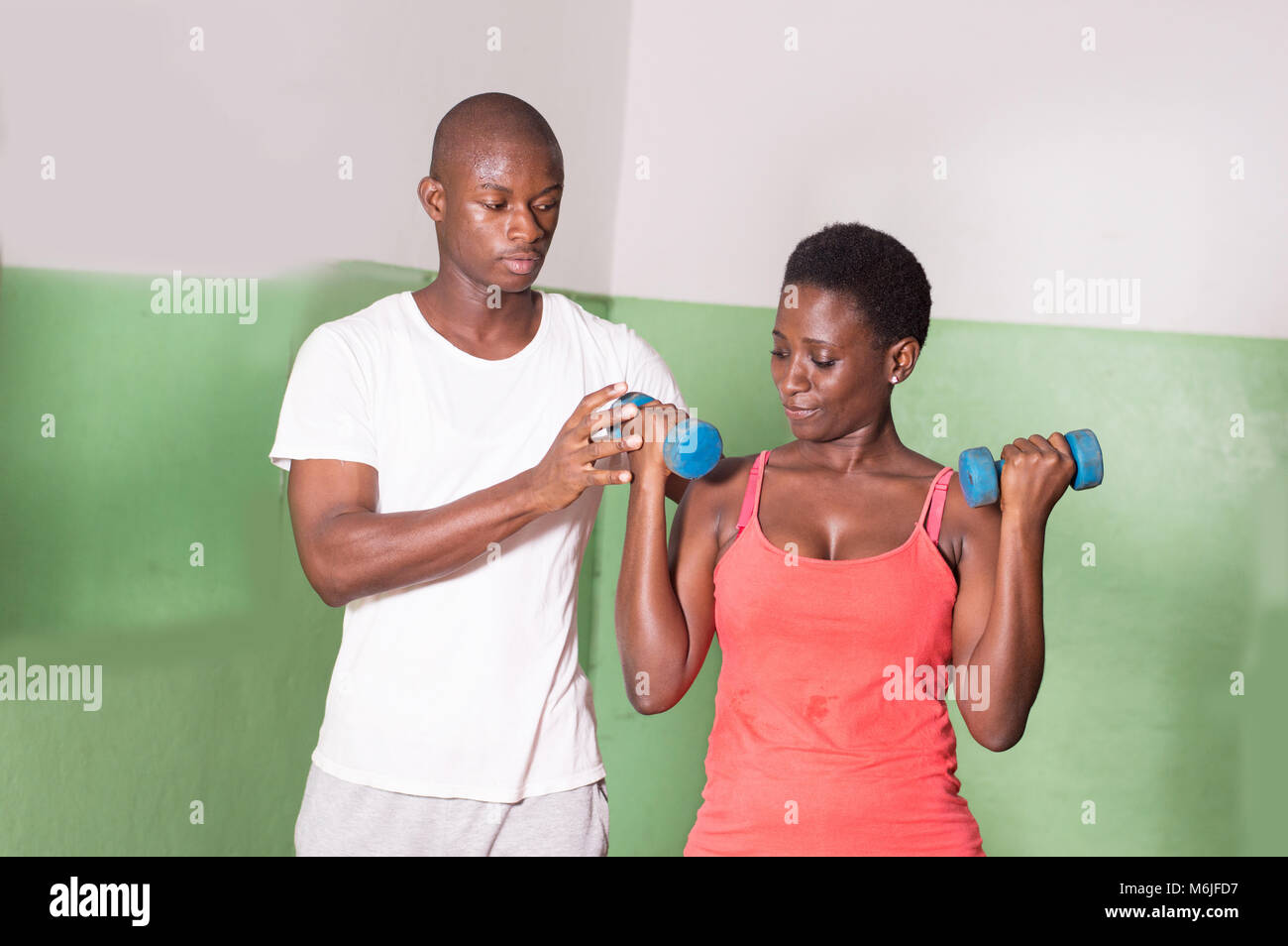 The gym trainer helps this young woman to practice in the studio. - Stock Image
